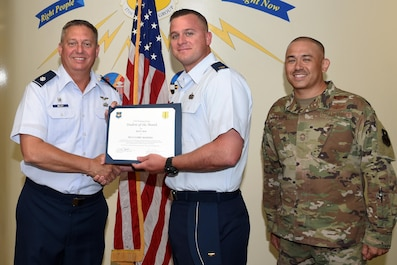 U.S. Air Force Lt. Col. Herbert Millet III, 313th Training Squadron commander, presents the 315th Training Squadron Officer Student of the Month award to 2nd Lt. Cory Maffeo, 315th TRS student, at the Brandenburg Hall on Goodfellow Air Force Base, Texas, August 2, 2019. The 315th TRS's vision is to develop combat-ready intelligence, surveillance and reconnaissance professionals and promote an innovative squadron culture and identity unmatched across the U.S. Air Force. (U.S. Air Force photo by Airman 1st Class Abbey Rieves/Released)