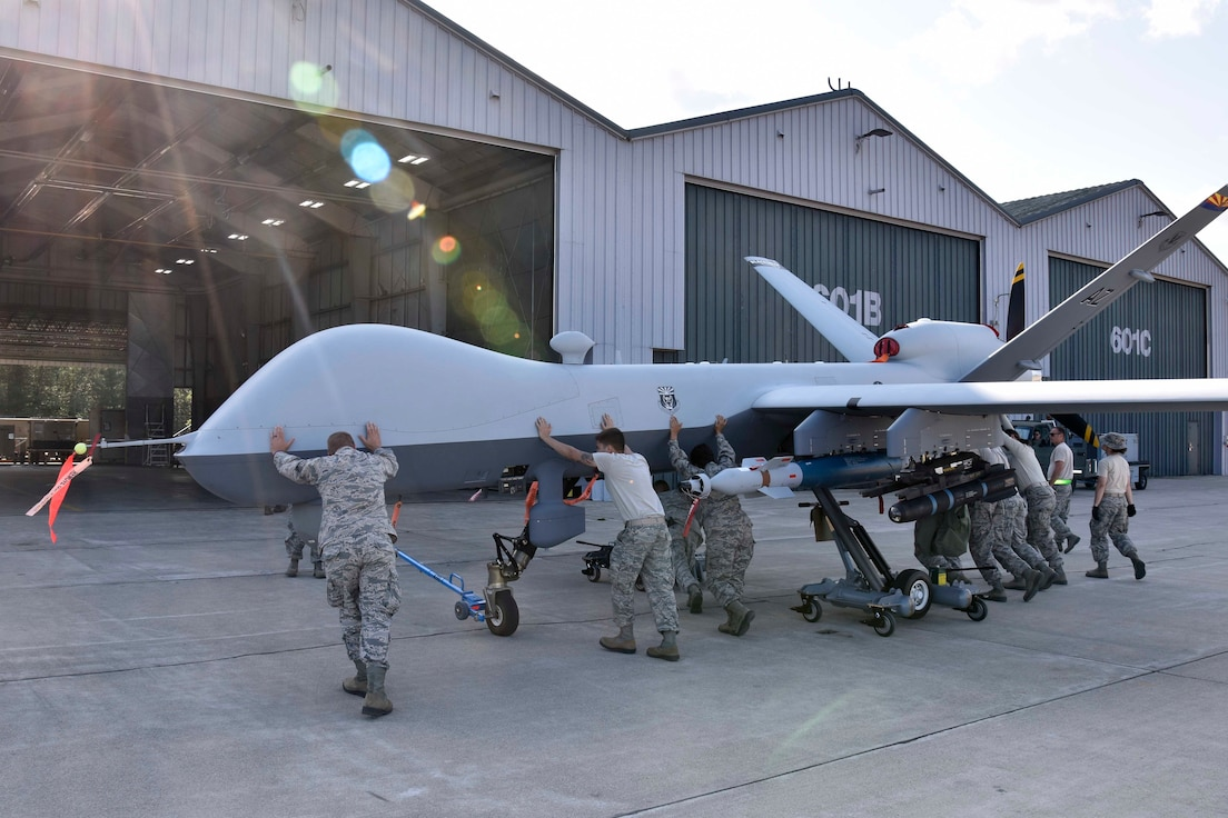 Members of the 214th Aircraft Maintenance Squadron, launch recovery element, work together to push an MQ-9 Reaper into a hanger during the Northern Strike19 exercise at the Alpena Combat Readiness Training Center, Mich., July 22, 2019. Northern Strike 19 is a National Guard Bureau-sponsored exercise uniting approximately 5,700 service members and more than 20 states and seven coalition countries at the Camp Grayling Joint Maneuver Training Center and the Alpena CRTC, both located in Northern Michigan. (U.S. Air National Guard photo by Senior Airman Ryan Zeski)