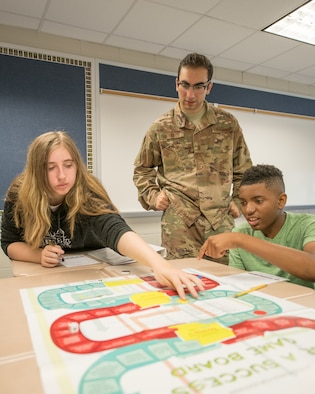 2nd Lt. George Nifakos, 436th Comptroller Squadron deputy budget officer, assists two Caesar Rodney High School freshmen with the Be a Success board game by Junior Achievement USA June 31, 2019, at Caesar Rodney High School in Camden, Del. The game teaches players about plotting career paths, pursuing education, entering the workforce and, ultimately, reaching their financial goals. (U.S. Air Force photo by Mauricio Campino)