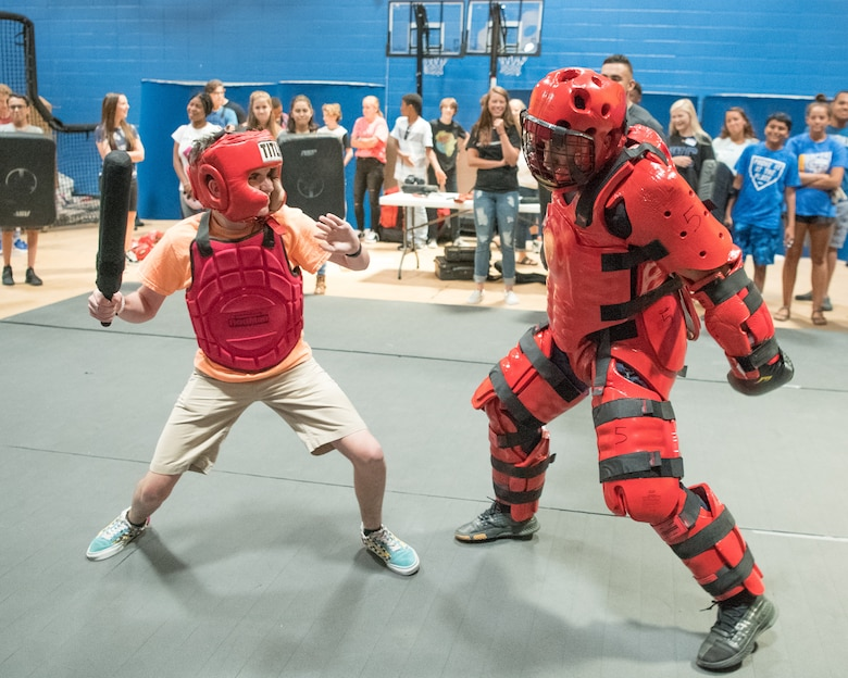 """Senior Airman John Paul C. Zografos, 436th Security Forces Squadron Raven, wears a """"Red Man"""" suit during a sparring session against a Caesar Rodney High School freshman June 31, 2019, at Caesar Rodney High School in Camden, Del. Over 30 Dover AFB Airmen visited the school to share their Air Force career experiences and teach the students skills to help them excel in the workplace. (U.S. Air Force photo by Mauricio Campino)"""