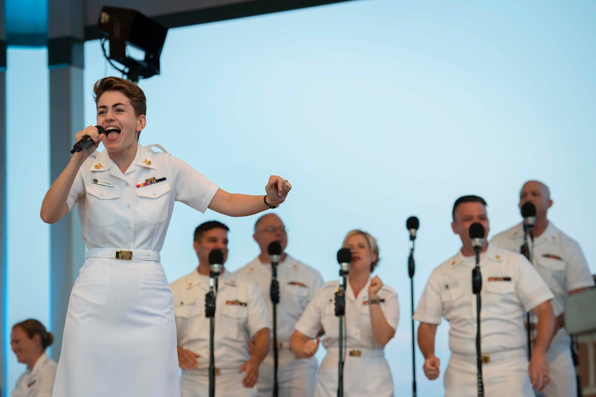 A sailor sings  with other people singing in the background.