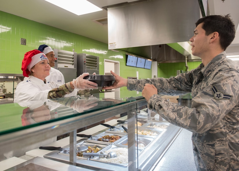 Gen. Maryanne Miller, left, commander of Air Mobility Command, and Chief Master Sgt. Terrence Greene, AMC command chief master sergeant, serve an Airman food at the Gaylor Dining Facility during a visit to Joint Base Charleston, South Carolina, July 30, 2019. Miller and Greene visited JB Charleston July 29 to August 1 to get a first-hand look at mission capabilities, new innovative programs and how JB Charleston is taking care of its service members to build a stronger mobility force.  The dining facility re-opened February 2019 after a two-year renovation. The renovations help dining facility personnel adjust to changing dietary needs and preferences, and improves efficiency and reduces costs while maintaining mission feeding capabilities.