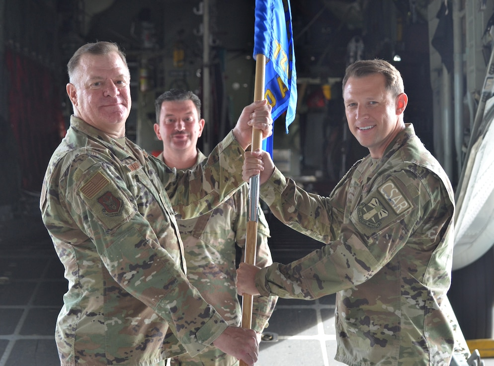 Two men holding the unit flag with a man standing behind them. They are looking at the camera and smiling.