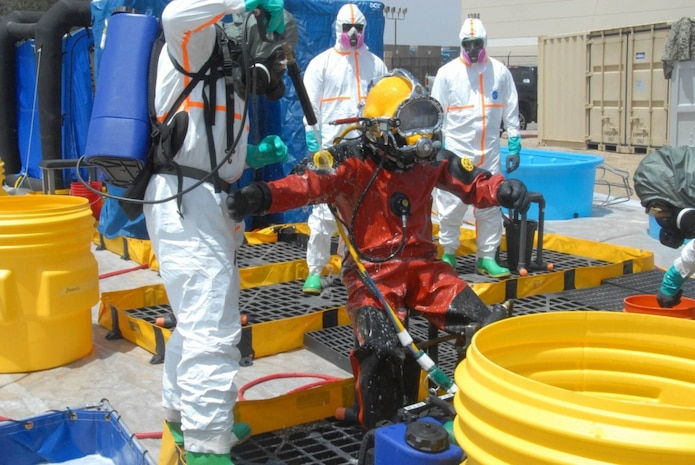 """PORT HUENEME, Calif. """" Petty Officer 2nd Class Zachary Schulte, NAVFAC EXWC, being decontaminated utilizing the ESSM DECON Kit during a contaminated water dive scenario as part of CONDIVEX 2019. NAVFAC EXWC Dive Locker hosts a Contaminated Water Diving Exercise. The 1-week event included a multi-service emergency response and multiple casualty incident scenario as part of Coastal Trident 2019 to support U.S. Navy science and technology initiatives. EXWC divers and support personnel participated in low-risk diving exercises to help evaluate and develop technologies to meet Fleet needs. (Official Navy photos by: Builder 1st Class Jesus Saucedo) /Released"""