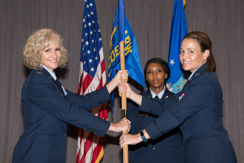 Colonel Jeanette Frantal, 42nd Medical Group commander, hands the unit flag for the 42nd Health Care Operations Squadron to Lt. Col. Melissa Runge, HCOS commander, during a medical group squadrons' re-designation ceremony Aug. 5, 2019, Maxwell Air Force Base, Alabama. The 42nd Medical Operations Squadron was re-designated the 42nd HCOS, which will focus on military family member, non-active duty and retiree health care, as part of Defense Department reforms to the Military Health System. (U.S. Air Force photo by William Birchfield)
