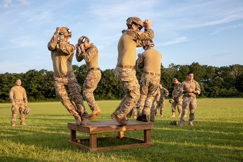 Four service members jump off a low wood platform in a field.