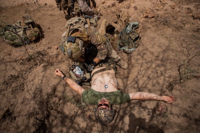 A U.S. Marine with Special Purpose Marine Air-Ground Task Force-Crisis Response-Africa 19.2, Marine Forces Europe and Africa, is treated for simulated injuries by a U.S. Air Force pararescue jumper during quick-reaction force training in Thiés, Senegal Aug. 5, 2019