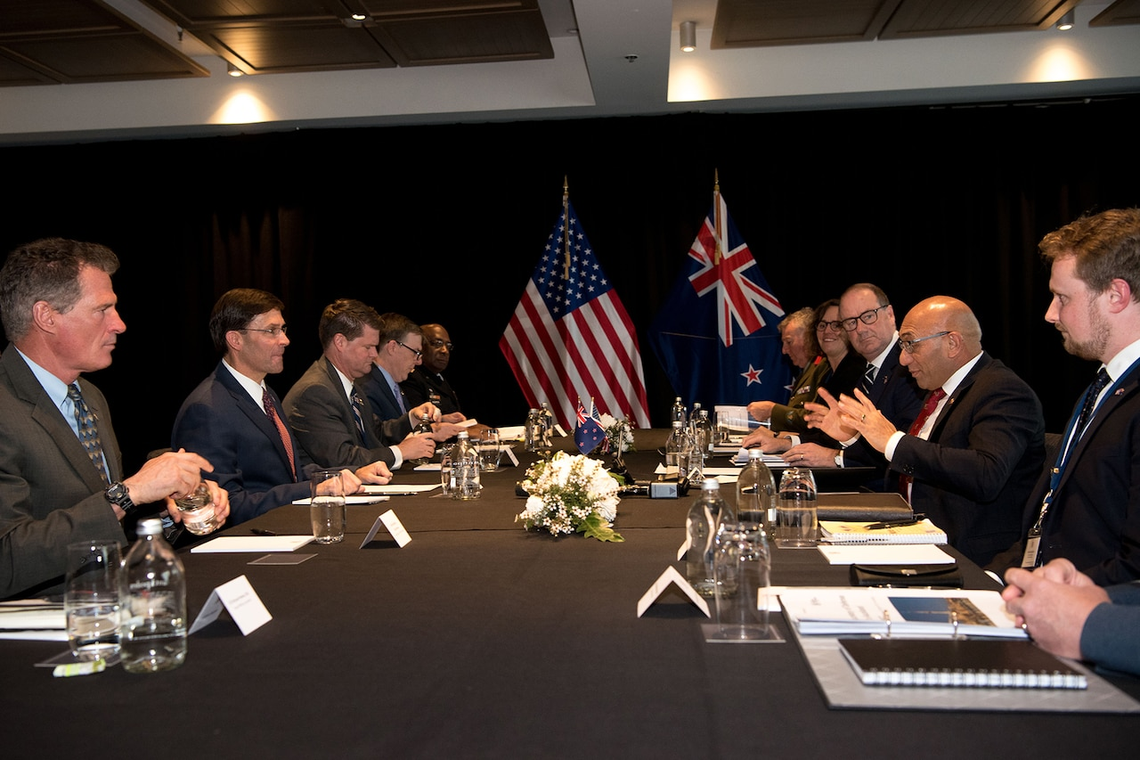 Two delegations sit on opposite sides of a table.