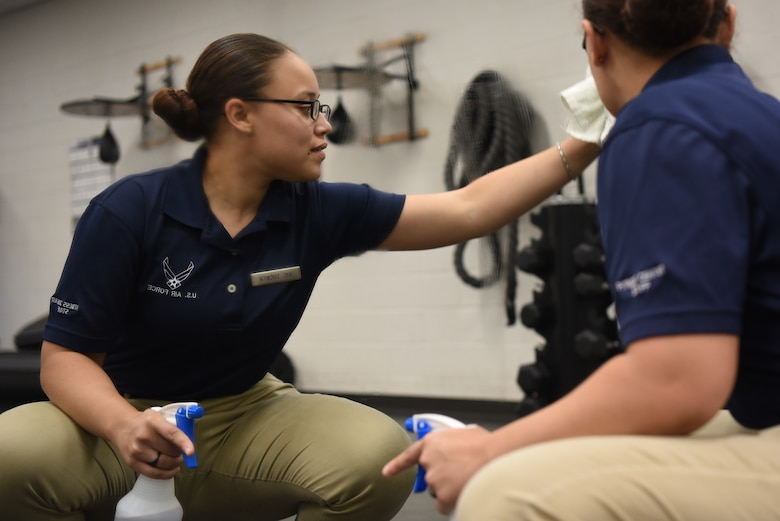 Airman 1st Class Sasha Tucker, 22nd Force Support Squadron fitness journeyman, cleans a mirror Aug. 6, 2019, at McConnell Air Force Base, Kan. The center is cleaned daily by the team of 15 Airmen who, re-rack weights, ensure all equipment is sanitized and do laundry hourly. These FSS Airmen keep the gym clean and functional for over 550 visitors daily. (U.S. Air Force photo by Airman 1st Class Alexi Myrick)