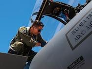 Capt. Samuel Wozniak enters an F-15E Strike Eagle.