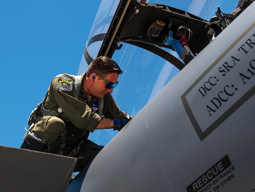 Capt. Samuel Wozniak enters an F-15E Strike Eagle.