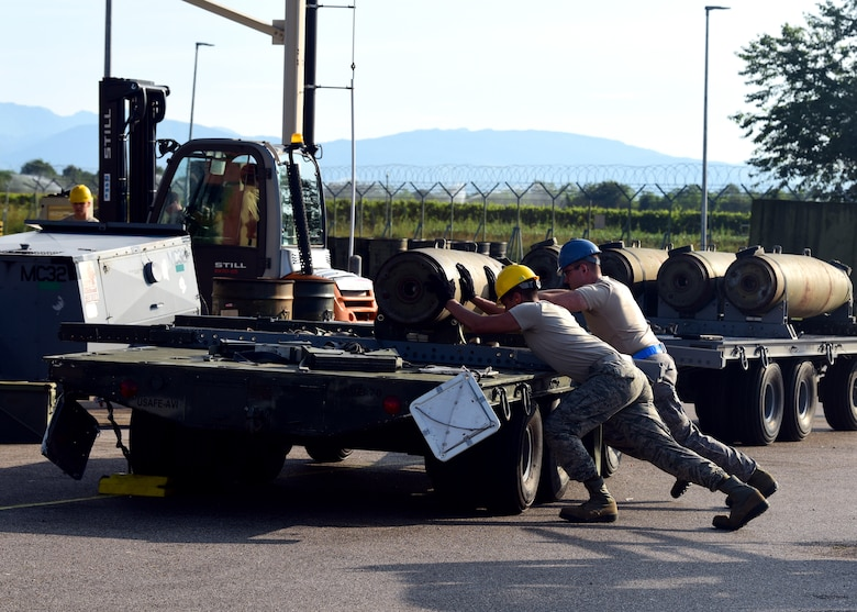 Airmen assist each other in loading munitions onto a trailer during Combat Ammunition Production Exercise 2019 on Aug. 7, 2019, at Aviano Air Base, Italy. Exercises such as CAPEX keep the Airmen of the munitions career field prepared and demonstrates USAFE's ability to be rapidly ready for contingency operations. (U.S. Air Force photo by Airman 1st Class Caleb House)