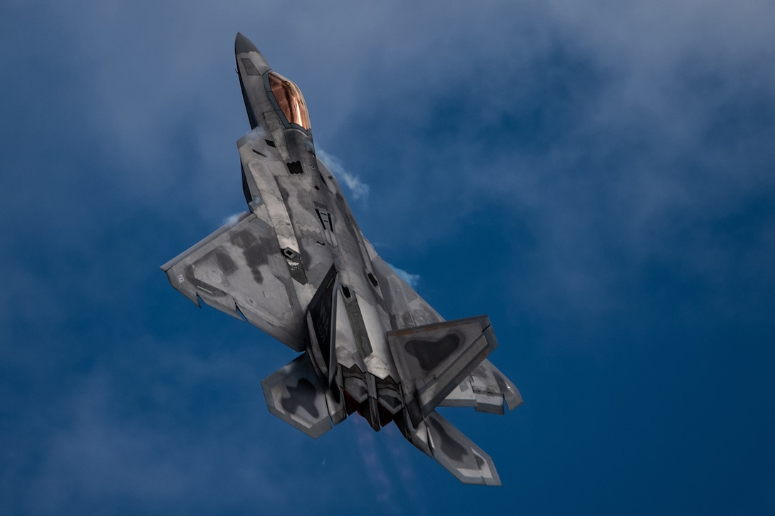 A military fighter jet flies against a blue sky.