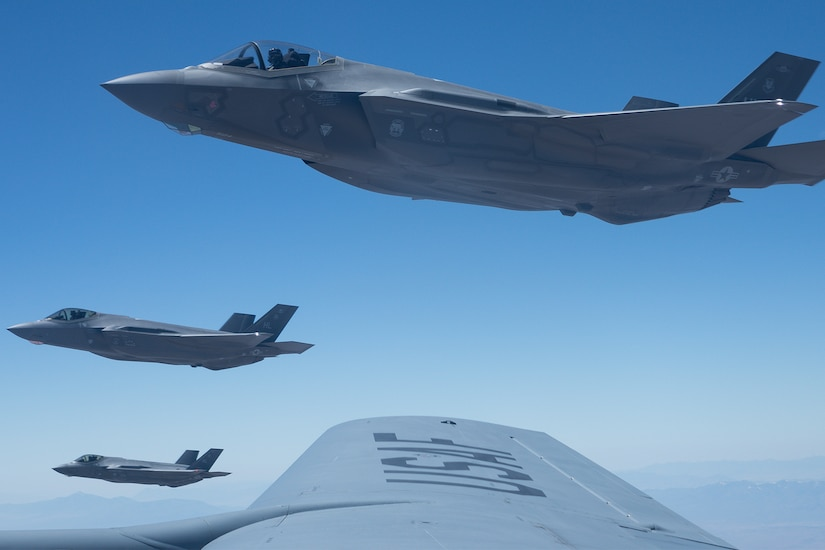 Three military fighter jets are seen off the wing of another military aircraft.