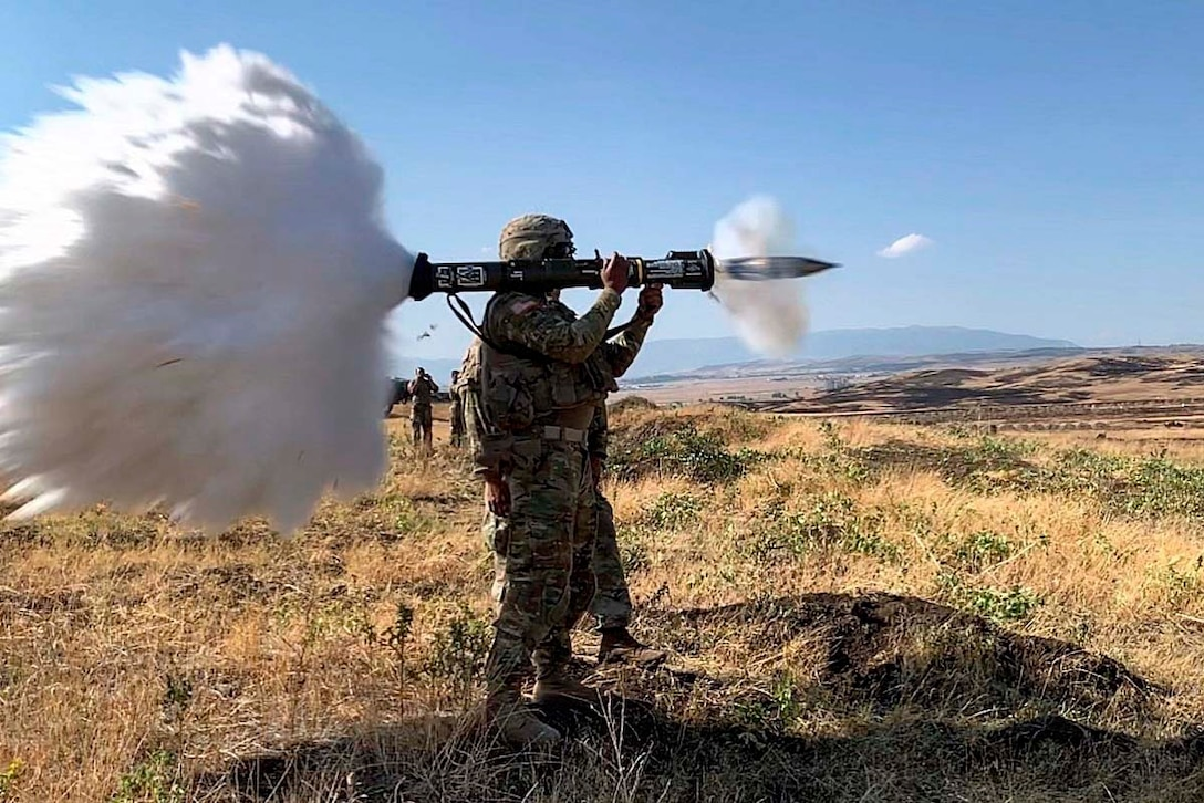 A soldier fires a large weapon from his shoulder.