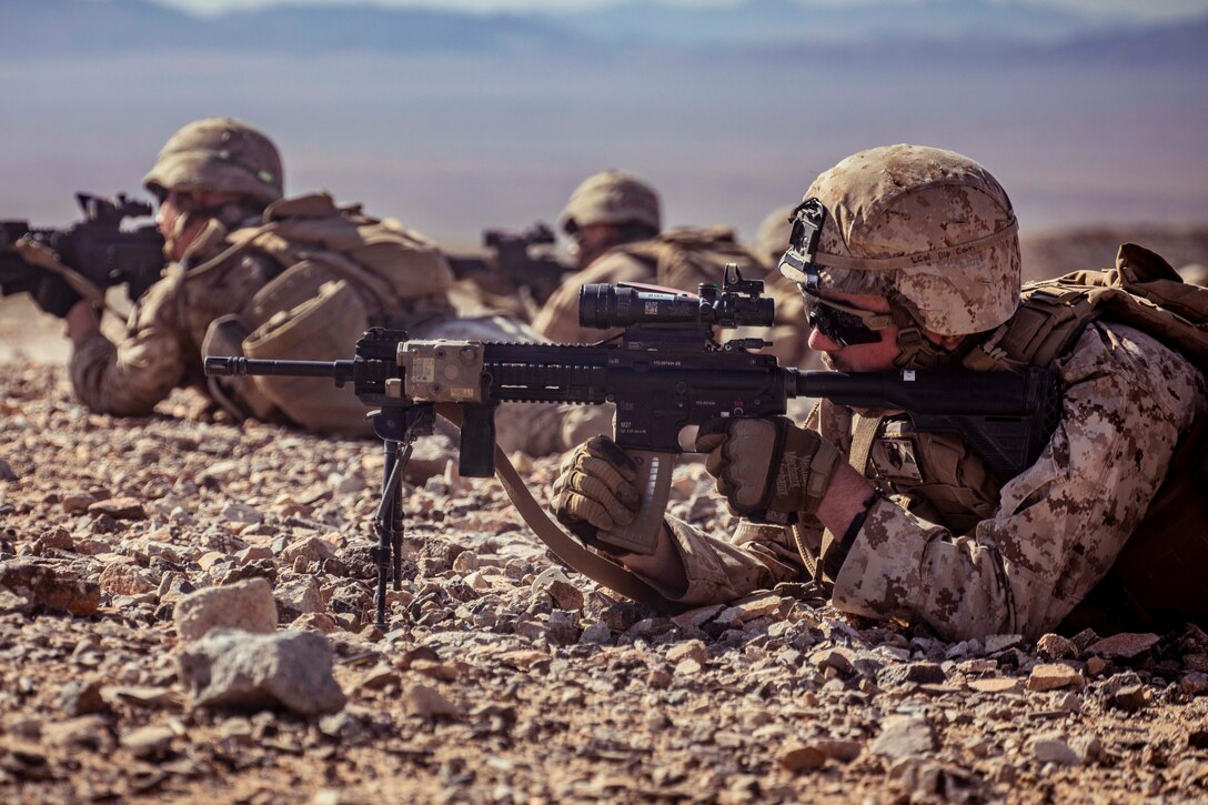 Marines lie on the ground firing weapons.