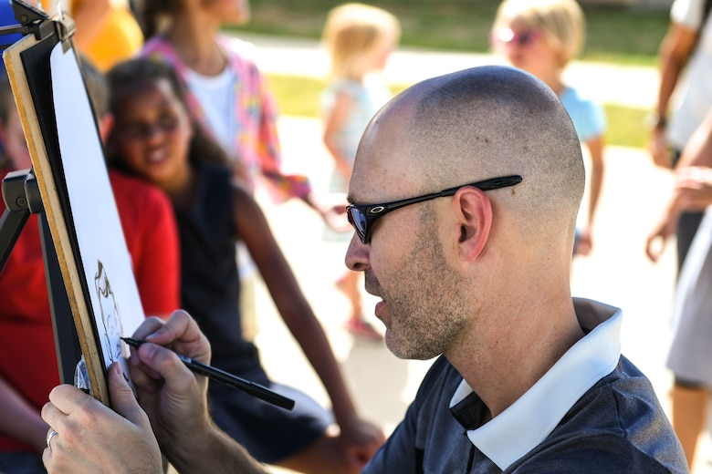 Jason Sauer, a denver caricatures artist, draws a sketch during the National Night Out event, Aug. 6, 2019, on Buckley Air Force Base, Colo. Sauer has 20 years of