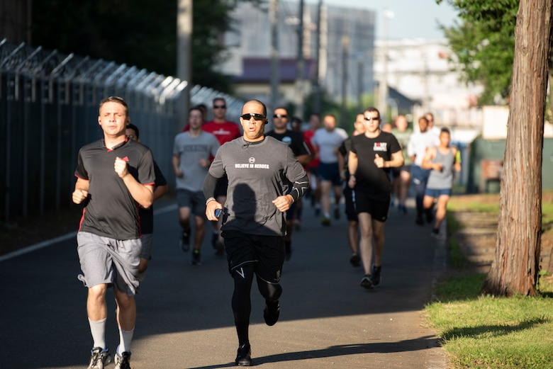 Master Sgt. Ryan Hines (center), 374th Logistics Readiness Squadron Fuels Environmental Safety Office section chief, and members of Team Yokota run during a 5K on Purple Heart Day at Yokota Air Base, Japan, Aug. 7, 2019.