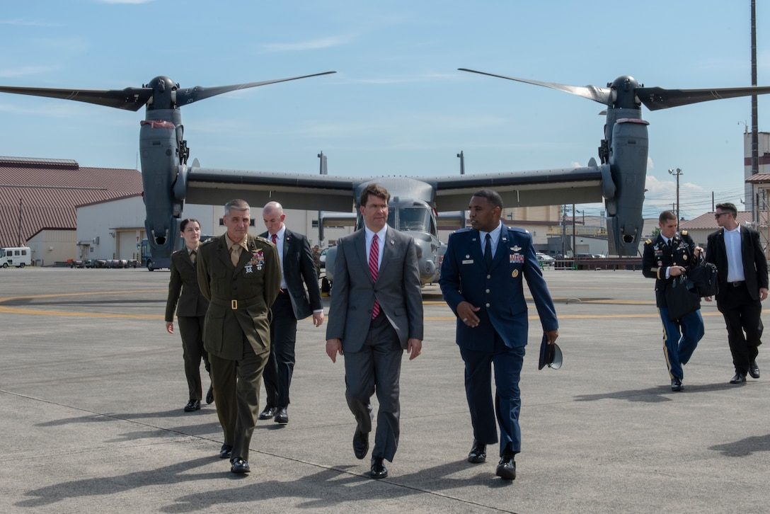 U.S. Secretary of Defense Dr. Mark T. Esper, center, walks with U.S. Marine Corps Maj. Gen. Christopher J. Mahoney, United States Forces Japan deputy commander, left, and U.S. Air Force Col. Otis C. Jones, 374th Airlift Wing commander, right, prior to departing Yokota Air Base, Japan to continue his Pacific Tour, Aug. 7, 2019.