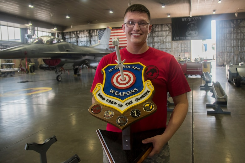 U.S. Air Force Senior Airman Cody Wilson, a 13th Aircraft Maintenance Unit load crew member, holds a trophy during the second quarter load crew competition at Misawa Air Base, Japan, Aug. 2, 2019. The 13th AMU weapons load crew Airmen took home the trophy after being assessed on their performance and weapons load technical abilities. (U.S. Air Force photo by Takaharu Daibo)