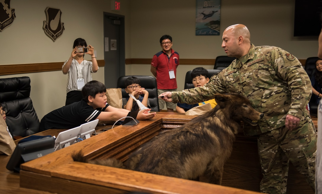 U.S. Air Force Chief Master Sgt. Steve Cenov, 8th Fighter Wing command chief, gives a local Korean child a security forces patch during a tour at Kunsan Air Base, Republic of Korea, Aug. 2, 2019. More than 20 children from the surrounding area were invited to tour the base and visit some of the facilities and organizations, such as the 8th Civil Engineer Squadron fire department. (U.S. Air Force photo by Senior Airman Stefan Alvarez)