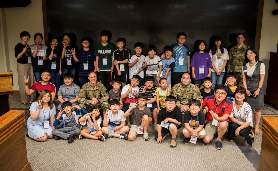 Korean children from the local area take a photo with 8th Fighter Wing leadership during a tour at Kunsan Air Base, Republic of Korea, Aug. 2, 2019. During their visit, the kids had a chance to get hands-on with some firefighting equipment and see one of the fire trucks use its water cannon. (U.S. Air Force photo by Senior Airman Stefan Alvarez)