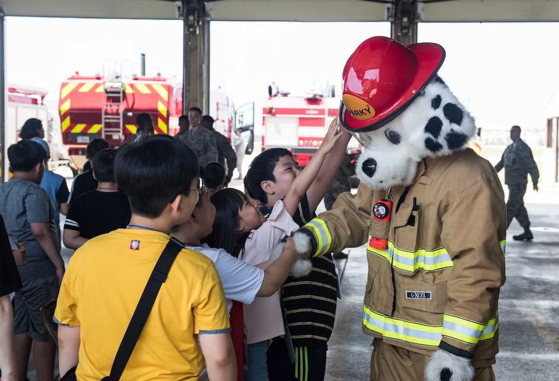 Korean children from the local area greet Sparky, the 8th Civil Engineer Squadron fire department mascot, during a tour at Kunsan Air Base, Republic of Korea, Aug. 2, 2019. Their visit included a chance to get hands-on with some firefighting equipment and see one of the fire trucks use its water cannon. (U.S. Air Force photo by Senior Airman Stefan Alvarez)