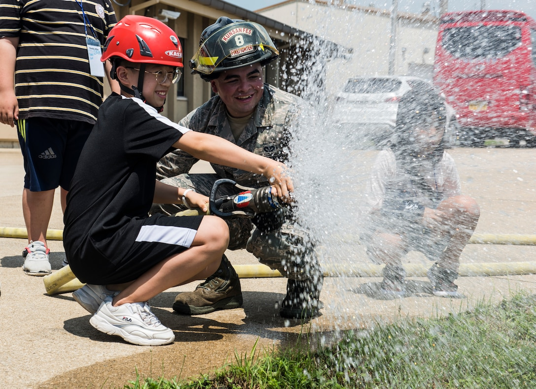 U.S. Air Force Senior Airman Jacob Levee, 8th Civil Engineer Squadron firefighter, helps a Korean child operate a fire hose during a tour at Kunsan Air Base, Republic of Korea, Aug. 2, 2019. Their visit included a chance to get hands-on with some firefighting equipment and see one of the fire trucks use its water cannon. (U.S. Air Force photo by Senior Airman Stefan Alvarez)