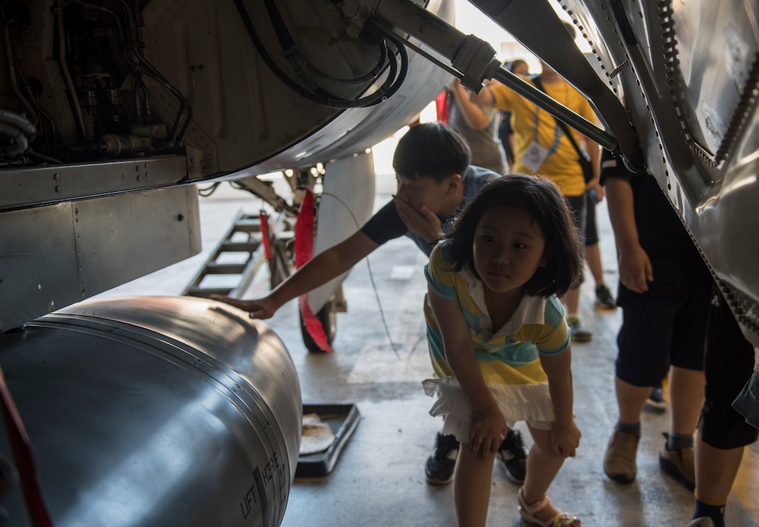 Korean children from the local area examine an F-16 Fighting Falcon during a tour at Kunsan Air Base, Republic of Korea, Aug. 2, 2019. The tour ended with the children getting up close and personal with one of the 8th Fighter Wing's aircraft, and a demonstration from the 8th Aircraft Maintenance Squadron on loading the F-16. (U.S. Air Force photo by Senior Airman Stefan Alvarez)