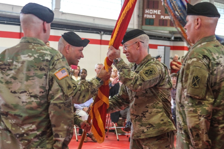 Lt. Gen. Christopher G. Cavoli, the commanding general of U.S. Army Europe (USAREUR) passes the 10th Army Air and Missile Command colors to Brig. Gen. Gregory J. Brady during a change of command ceremony Aug. 7 on Kleber Kaserne.