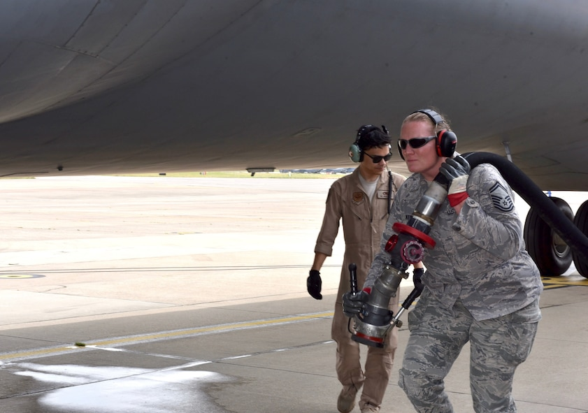 Airman pulls aircraft fuel hose over left shoulder and walks towards the front of aircraft.