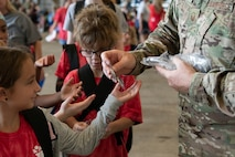 A military child participates in a Kids Deployment Line.