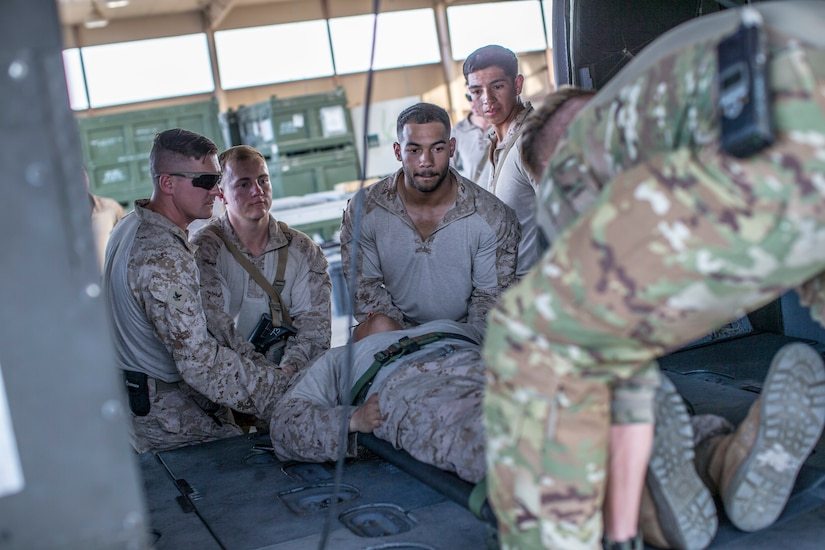 U.S. Sailors with the 11th Marine Expeditionary Unit, and a U.S. Soldier with Golf Company, 5th Battalion, 159th Aviation Regiment load a simulated casualty onto an HH-60M helicopter during a joint-service casualty evacuation class at Camp Buehring, Kuwait. The Boxer Amphibious Ready Group and the 11th MEU are deployed to the U.S. 5th Fleet area of operations in support of naval operations to ensure maritime stability and security in the Central Region, connecting the Mediterranean and the Pacific through the Western Indian Ocean and three strategic choke points.