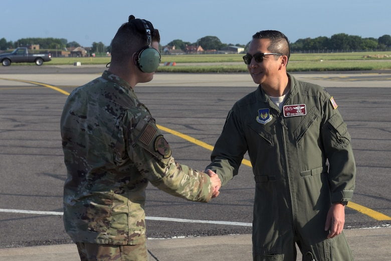 Col. Troy Pananon, 100th Air Refueling Wing commander, shakes hands with Senior Airman Alfonso Hernandez, 100th Aircraft Maintenance Squadron crew chief, at RAF Mildenhall, England Aug. 6, 2019. Pananon and Hernandez performed a walkaround inspection of the KC-135 Stratotanker prior to departure to Spain. (U.S. Air Force photo by Senior Airman Benjamin Cooper)