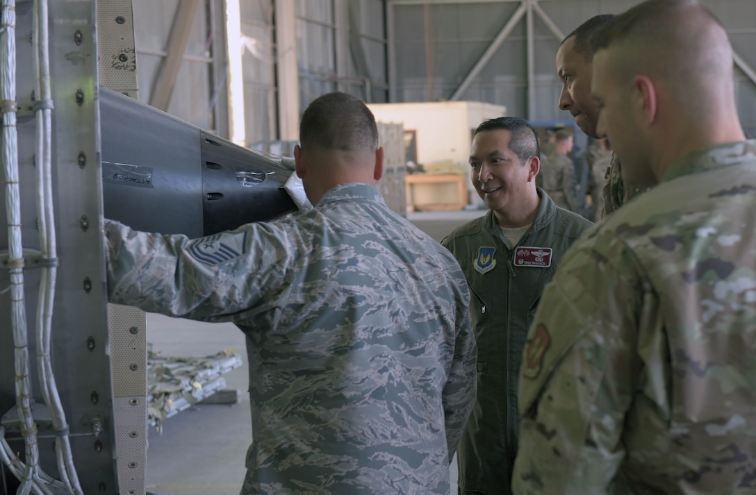 Col. Troy Pananon, 100th Air Refueling Wing commander, speaks with deployed Airmen attached to the 351st Expeditionary Air Refueling Squadron, at Moron Air Base, Spain, Aug. 6, 2019. The Airmen were explaining the condition of a KC-135 Stratotanker engine under repair. (U.S. Air Force photo by Senior Airman Benjamin Cooper)