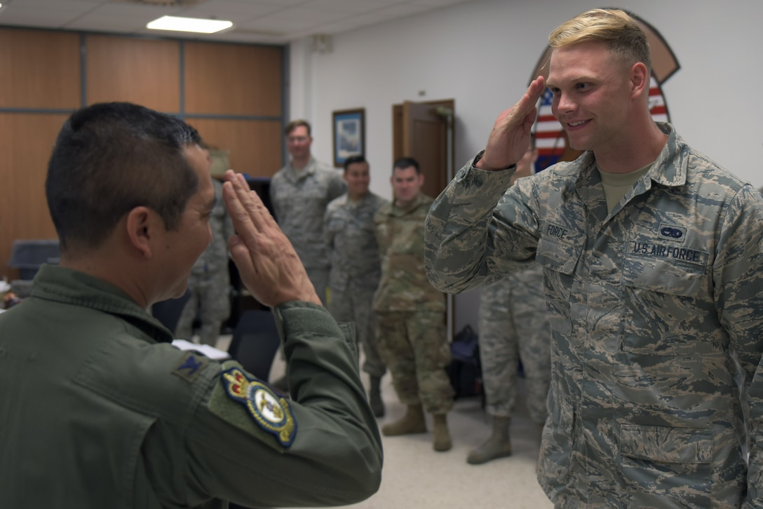 Col. Troy Pananon, 100th Air Refueling Wing commander, salutes Senior Airman Michael Force, 351st Expeditionary Air Refueling Squadron environmental electrical journeyman, at Moron Air Base, Spain, Aug. 6, 2019. Force had just been coined by Pananon for his outstanding work during the deployment. (U.S. Air Force photo by Senior Airman Benjamin Cooper)