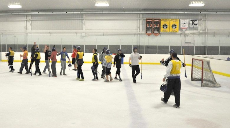 Members of the 38th Reconnaissance Squadron congratulate each other by high-fiving after a game of Broomball June 21, 2019, at Grover Ice Rink, Omaha, Nebraska. The squadron participated in this unit cohesion event funded by the Unite Program. The program is the vision of Gen. David L. Goldfein, Air Force chief of staff, who recognized the need to take care of our squadrons by allowing units to focus on resiliency and cohesion for its members.