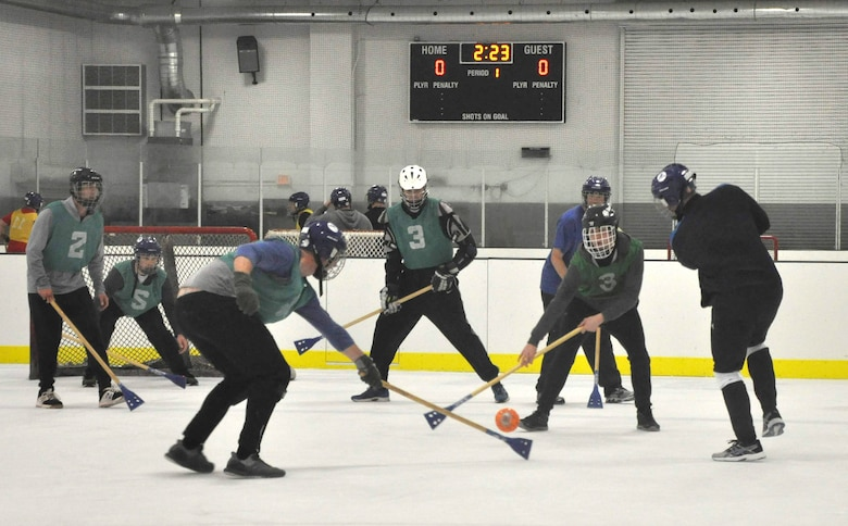 Members of the 38th Reconnaissance Squadron fight for the ball during a game of Broomball June 21, 2019, at Grover Ice Rink, Omaha, Nebraska. The squadron participated in this unit cohesion event funded by the Unite Program. The program is the vision of Gen. David L. Goldfein, Air Force chief of staff, who recognized the need to take care of our squadrons by allowing units to focus on resiliency and cohesion for its members.