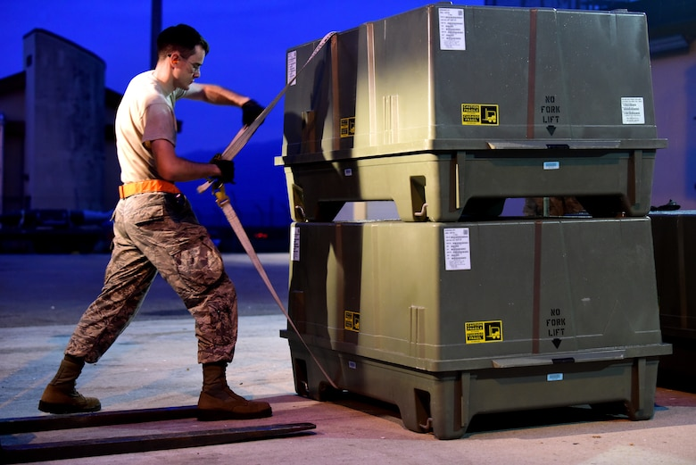 An Airman straps containers together allowing for safe and secure movement of materials during Combat Ammunition Production Exercise 2019 on Aug. 7, 2019, at Aviano Air Base, Italy. Conducting exercises such as CAPEX enables Airmen to learn in a controlled environment, bolstering unit interoperability and refining their practice. (U.S. Air Force photo by Airman 1st Class Caleb House)