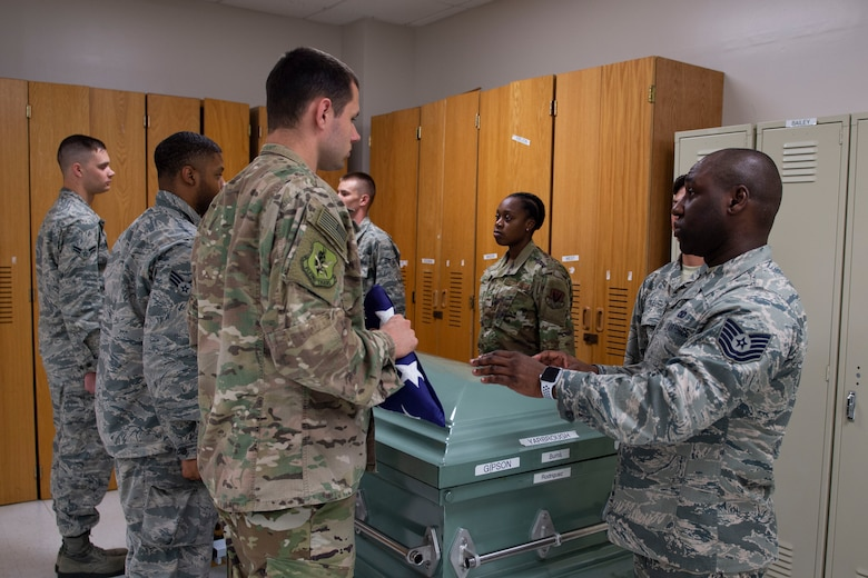 Tech. Sgt. Jesse Larson, left, NCO in charge (NCOIC) of Honor Guard, hands the flag to Tech. Sgt. Jamaal Smalls, NCOIC of Honor Guard, during six-person flag-fold training, July 25, 2019, at Moody Air Force Base, Ga. Smalls' experience as a master military training instructor helped him develop his professionalism and attention to detail that he now uses in Honor Guard. (U.S. Air Force photo by Airman Azaria E. Foster)