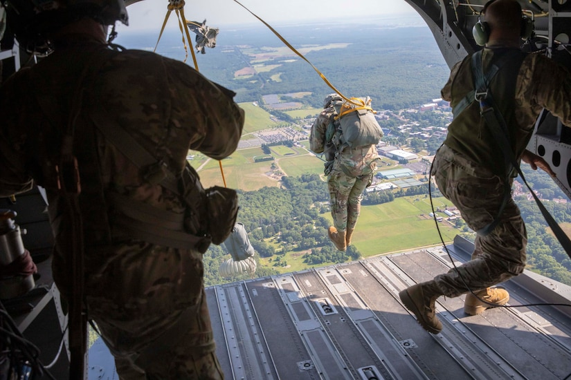 A soldier jumps out of plane while two other soldiers stand on either side inside the plane.