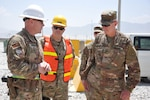 Navy Cmdr. Robert Kurkjian (center), commander of the DLA Support Team – Afghanistan, listens as Navy Lt. Cmdr. Steve Harrell, officer in in charge of DLA Disposition Services-Afghanistan; briefs Army Maj. Gen. John Sullivan, new commander of the 1st Theater Sustainment Command.
