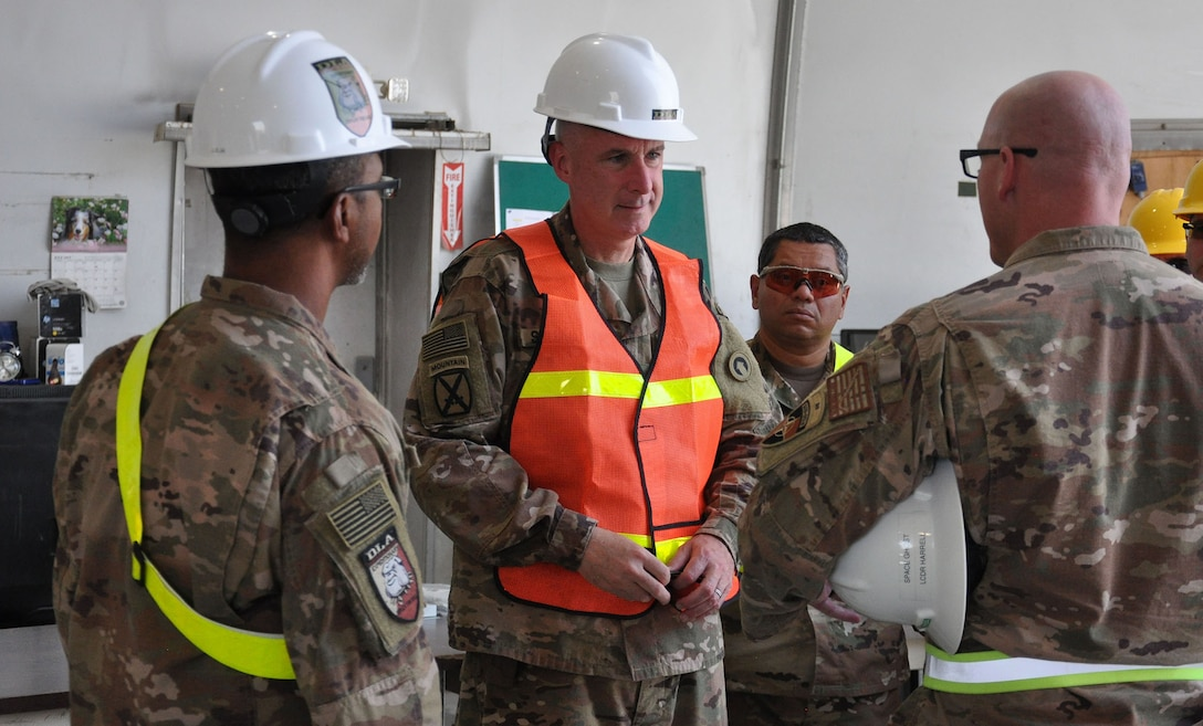 Army Maj. Gen. John Sullivan (center) listens as Navy Lt. Cmdr. Steve Harrell, officer in in charge of DLA Disposition Services-Afghanistan; briefs him before the tour in the receiving area of the Bagram DLA Disposition Services site.  Also shown are Jose Montanez (far left), Bagram site chief; and Navy Chief Petty Officer Michell Valencia (far right), Bagram deputy site chief.