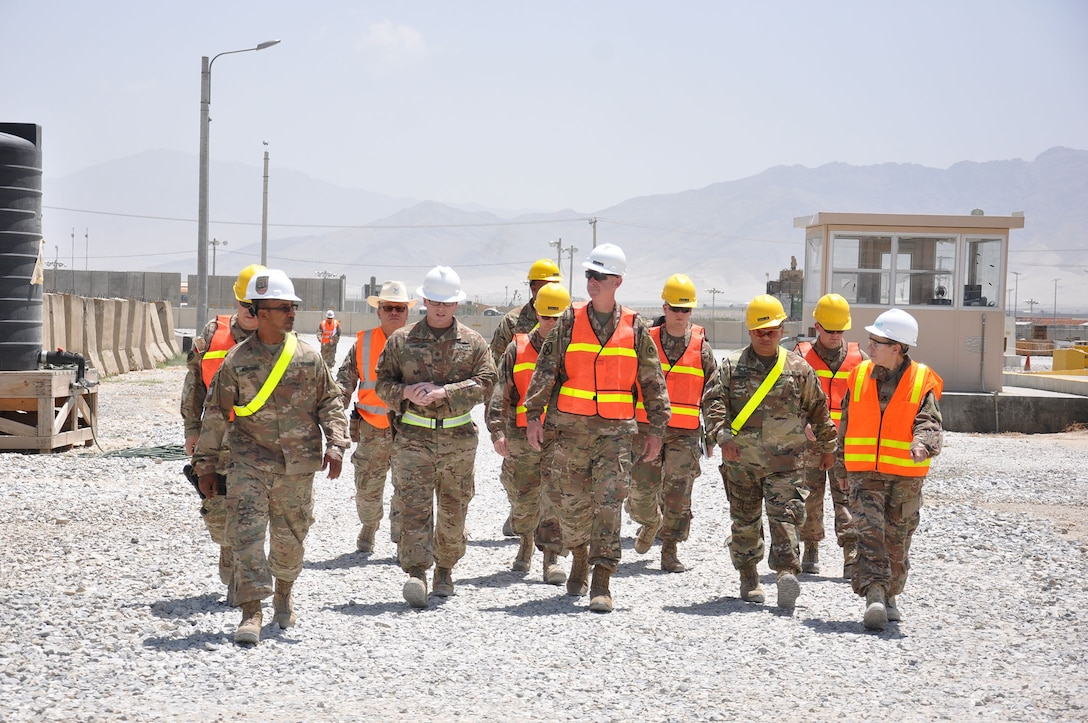 Navy Lt. Cmdr. Steve Harrell (left center), officer in in charge of DLA Disposition Services-Afghanistan; wraps up a tour of DLA Disposition Services site for Army Maj. Gen. John Sullivan (right center). Also shown in front row are Jose Montanez (far left), Bagram site chief; Navy Chief Petty Officer Michell Valencia (second from right) and Coleen Jewell, area manager. They are joined by other staff members walking behind them.