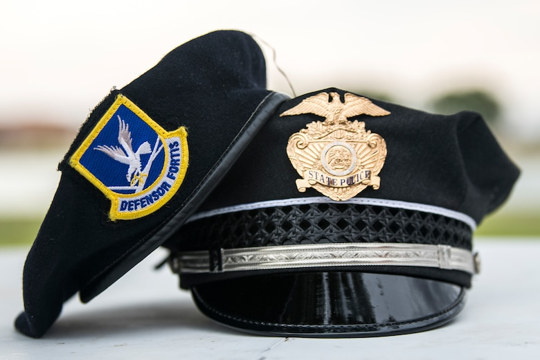 A beret from a defender assigned the 27th Special Operations Security Forces Squadron rests on a hat from a police officer assigned to the New Mexico State police at the National Night Out in Clovis, N.M., August 6, 2019. The National Night Out had members of the 27 SOSFS showcasing their talent with local and state police. (U.S. Air Force photo by Senior Airman Vernon R. Walter III)