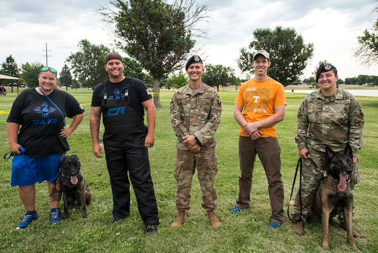Members of the 27th Special Operations Security Forces Squadron and Zia K-9 pose for a photo after performing a MWD and K-9 demonstration at the National Night Out in Clovis, N.M., August 6, 2019. The display showed the effectiveness of military working dogs and the discipline they have. (U.S. Air Force photo by Senior Airman Vernon R. Walter III)
