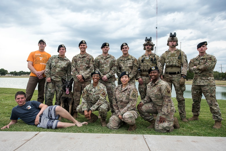 Members of the 27th Special Operations Security Forces Squadron pose for a photo after volunteering at the National Night Out in Clovis, N.M., August 6, 2019. The members hosted events such as a dunk tank, face painting, a military working dog demonstration and instructional course on the dangers of drunk driving. (U.S. Air Force photo by Senior Airman Vernon R. Walter III)