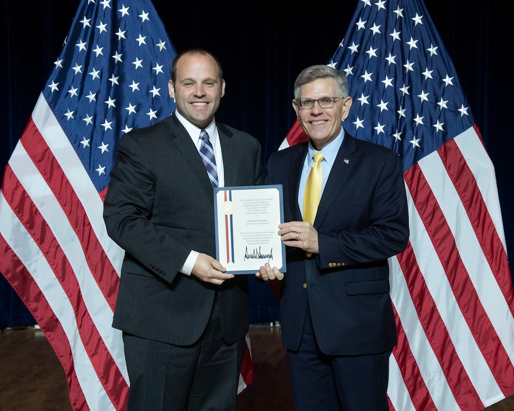 Dr. Daniel Garmann (left) received the Presidential Early Career Award for Scientists and Engineers from Kelvin Droegemeier, director of the Office of Science and Technology Policy, at a July 25, 2019, ceremony in Washington, DC.  (U.S. Department of Energy Photo/Donica Payne)