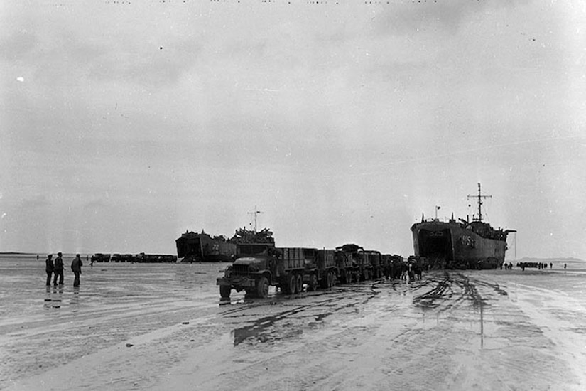 Two large ships deliver vehicles on a flat beachhead. Three men stand in the distance.