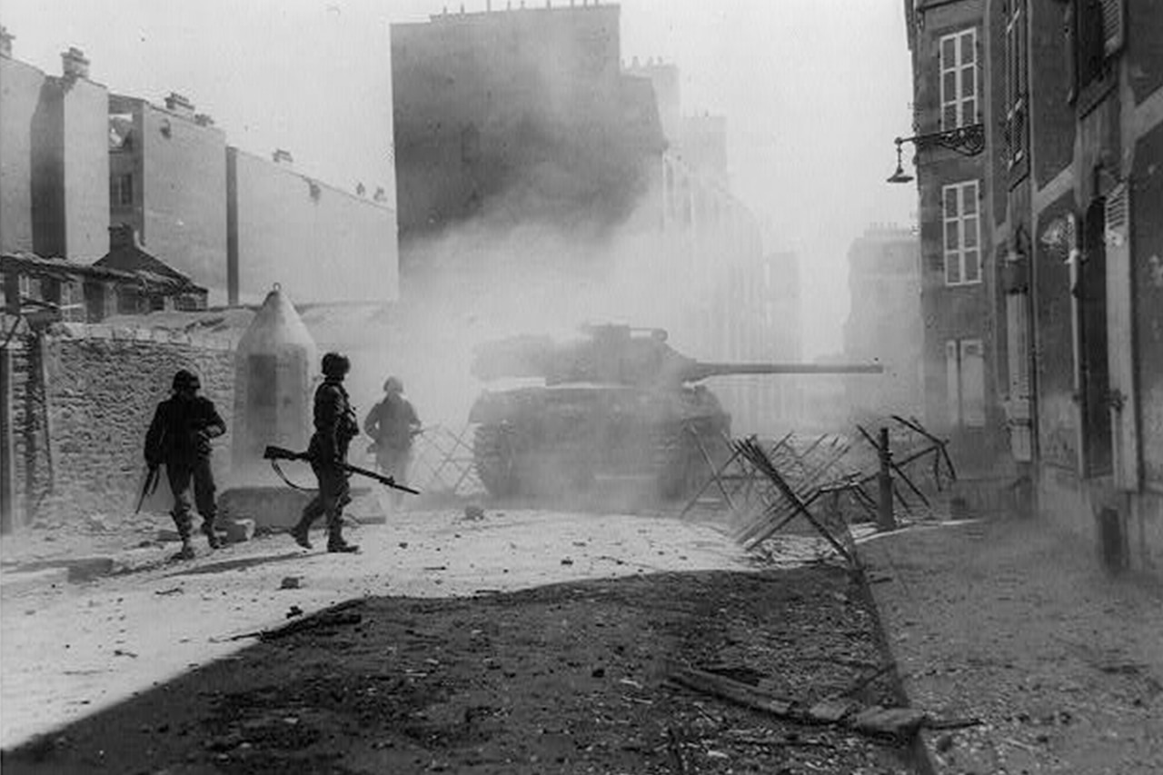 Three soldiers with rifles walk beside a tank along a tattered street in a town surrounded by several buildings.